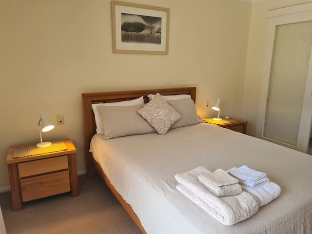 Main Bedroom with queen sized bed, linen covers / crisp white cotton or linen sheets: with view towards beautiful Bundjalong National Park, Snapper Bay / and ocean headlands. Access to walk-in wardrobe and 2nd bathroom through door at right.