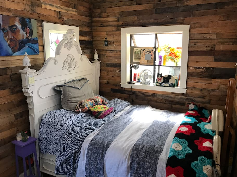 Cozy sleeping area includes a full bed, side table, fan, and reading light on garden window shelf. Note reclaimed pallet wood walls and garden window with plants.