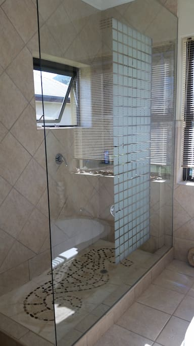 One of the en suite bathrooms which features a large walk in shower and sunken bath