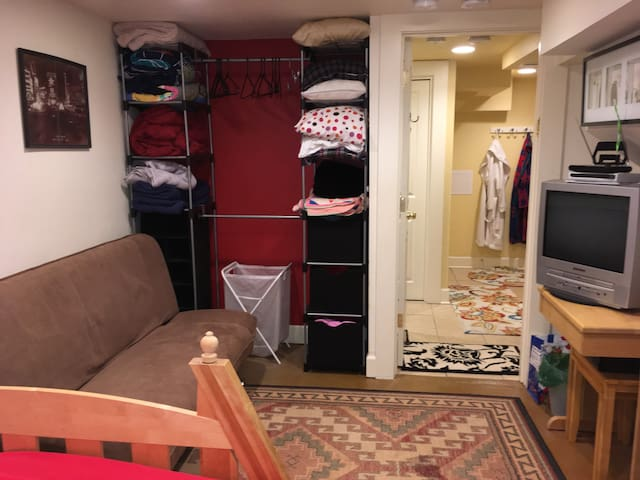 Bedroom front section with old school TV/DVD player, DVD collection, free-standing closet with hangers, and extra blankets and pillows.