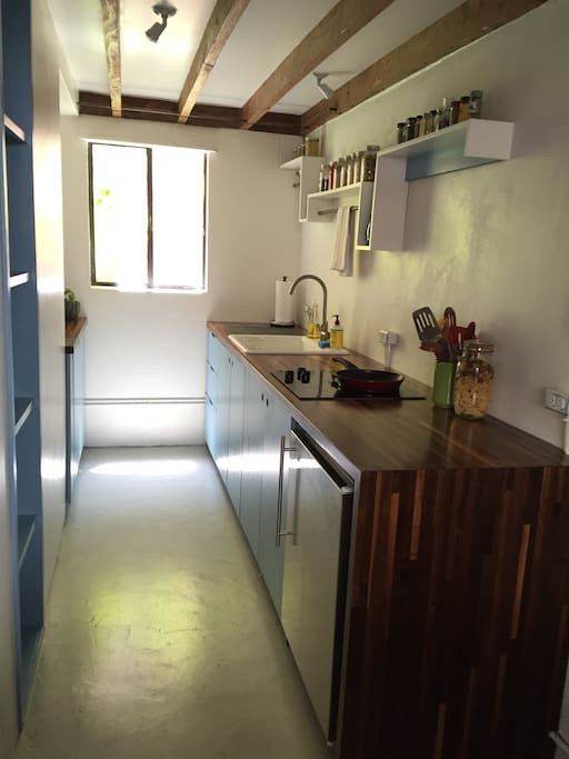 Cheerful galley kitchen with cooktop, under-counter fridge, microwave, toaster etc. Stocked with all of the essential dishwater and cookware.