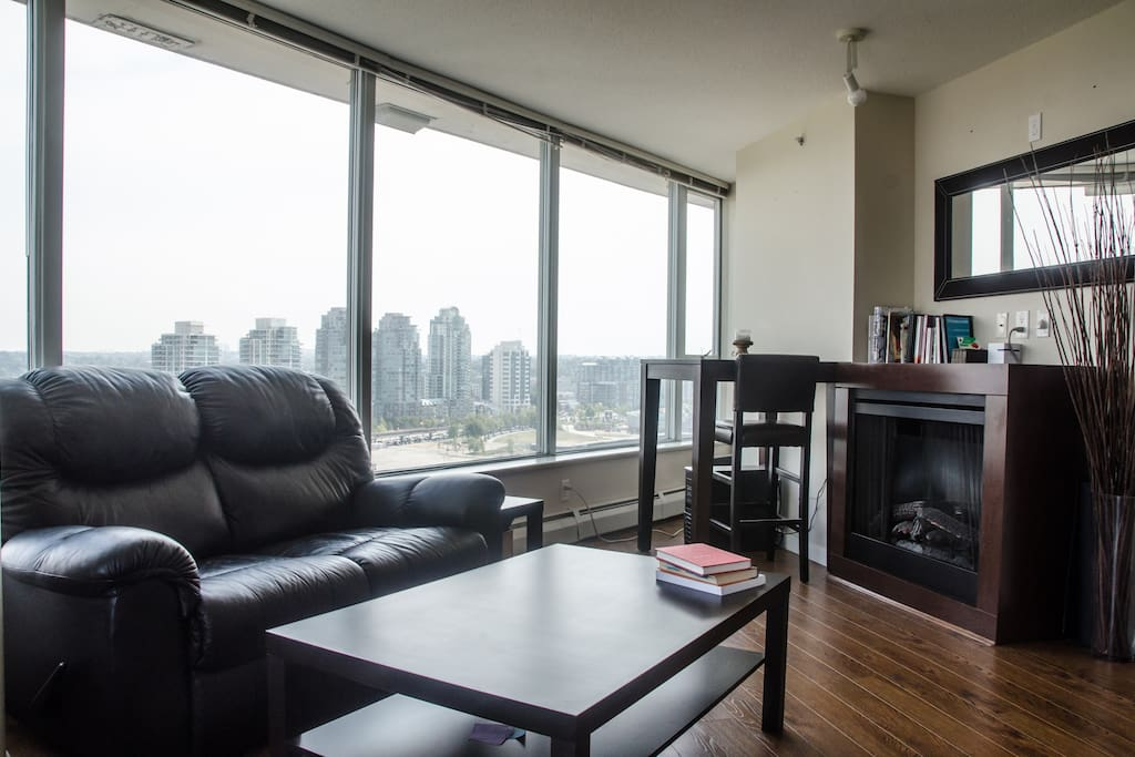 Open and spacious living room with an electric fireplace, table for two and panorama views.