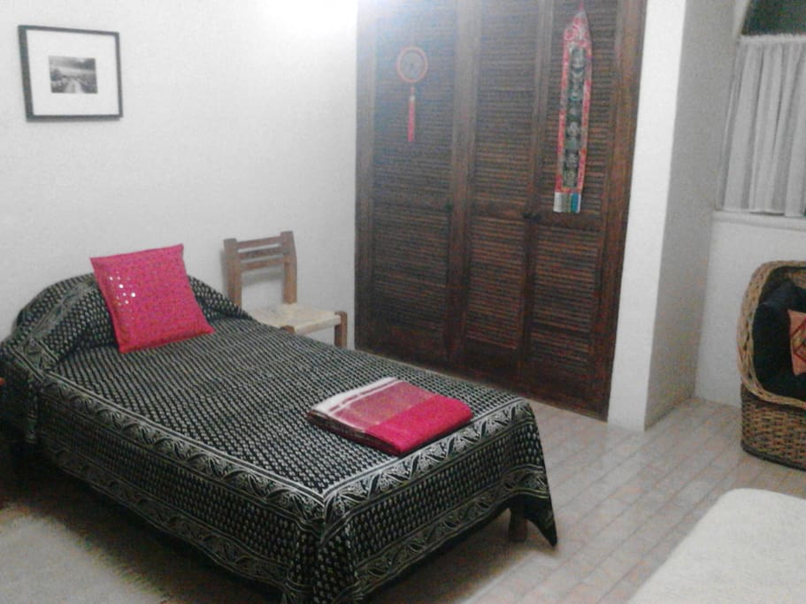 Private bedroom with sofa, small desk, three chairs, love seat, closet space.