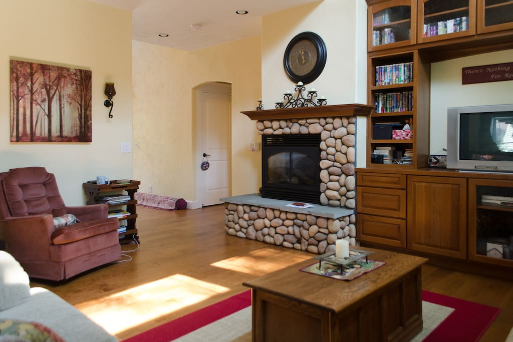 Comfortable reading corner in the Great Room near cozy two-sided natural gas riverrock fireplace.