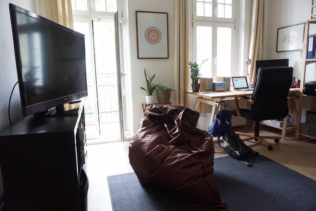 heller Wohnbereich mit Schreibtisch, TV und riesem Sitzsack