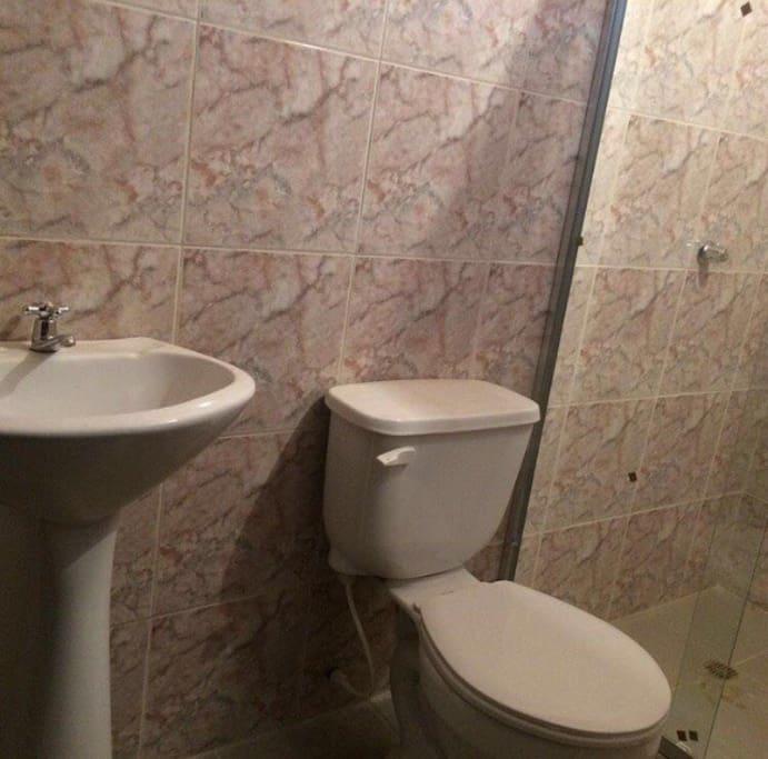 Baño privado, con puerta de la ducha en vidrio templado