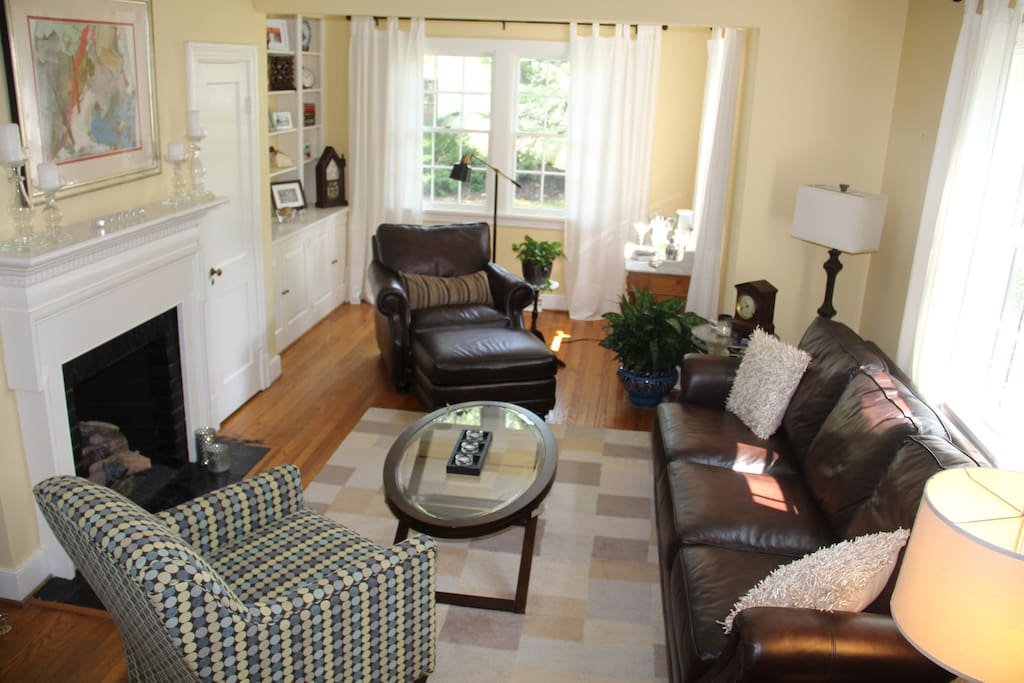Living Room with leather couch and chair/ottoman to enjoy fireplace for conversation, entertaining, and relaxation.