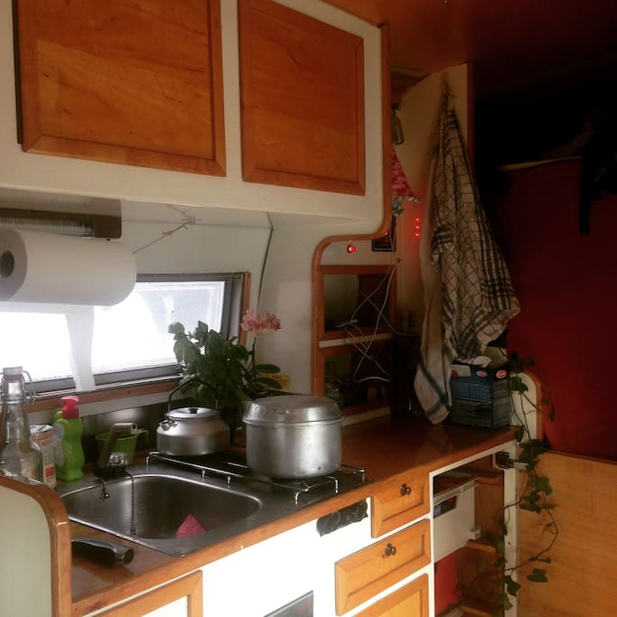 Fully equipped kitchen with sink, two flame stove and refrigerator.