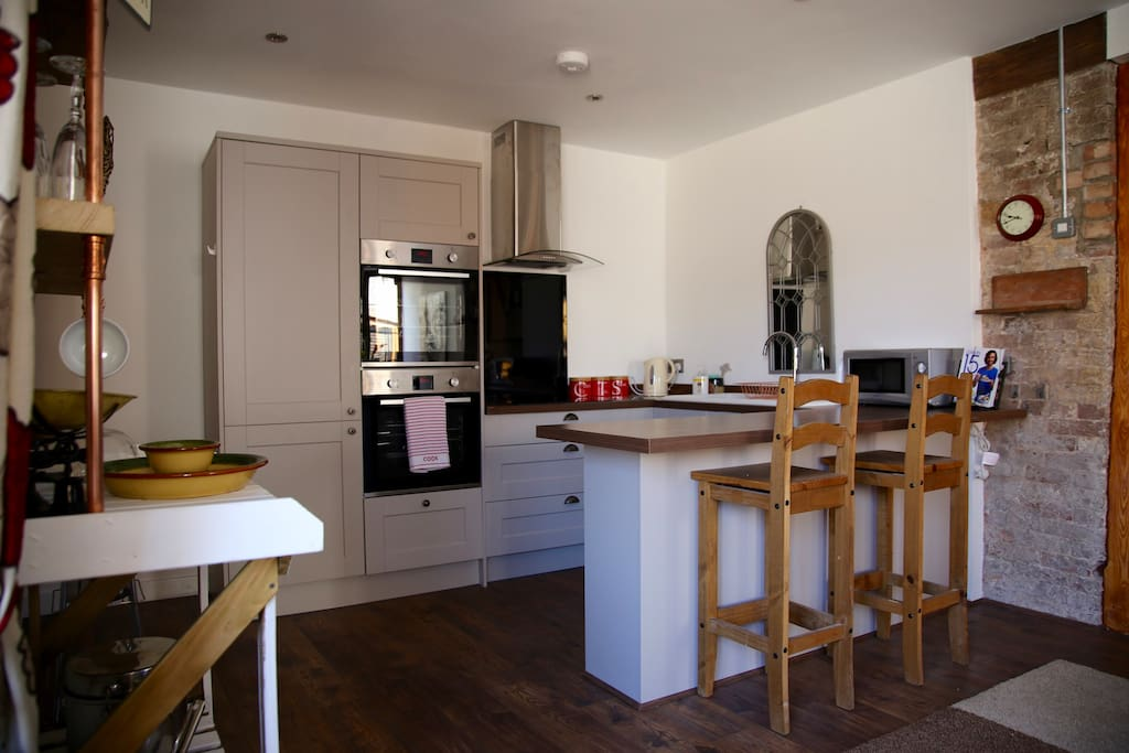 Open plan kitchen with double oven, dishwasher, microwave and breakfast bar