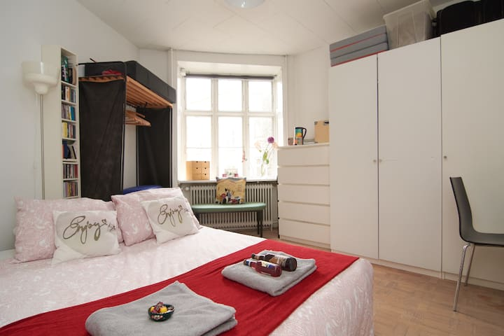 Room from door with wardrobes, window, bench, desk and comfortable sofa double bed
