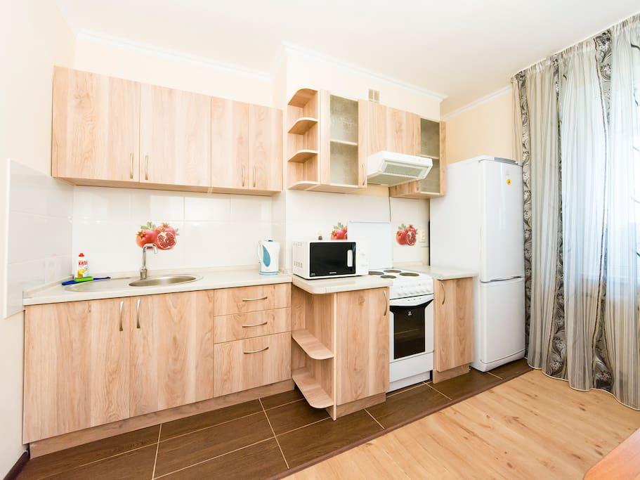 Кухонная плита, духовая печь, чайник, холодильник, столовые приборы, посуда, микроволновая печь.