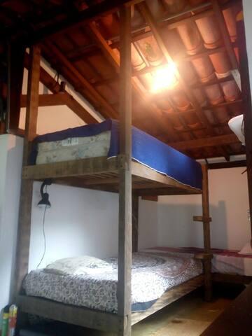 Quarto menor com beliche e cama de solteiro ao fundo