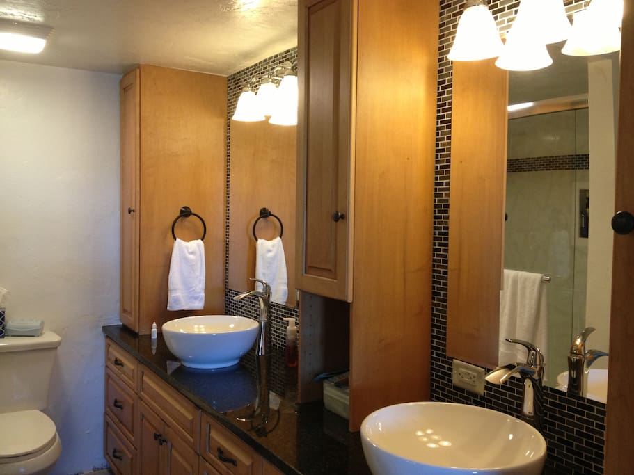 Master bath has double vessel sinks, stool and large walk-in shower.