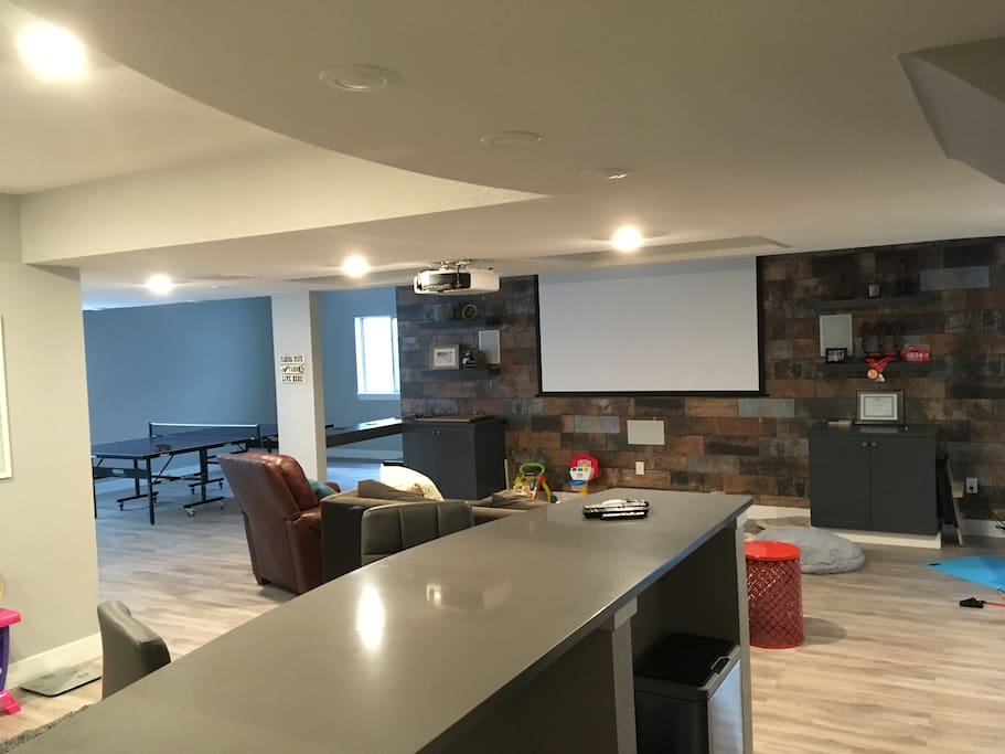 Basement area with projection screen, living area and bar (desk space) with sink and small refrigerator