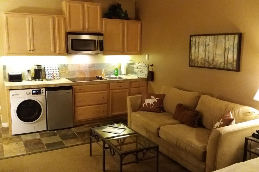 Queen size sleeper sofa, and a kitchen with sink, 4 burner cooktop, full size microwave, 4.3 cubic foot fridge, k-cup coffee maker, toaster, toaster oven, and a clothes washer/dryer combo unit.
