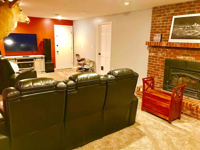 Shared space family room downstairs showing exit door and fireplace.