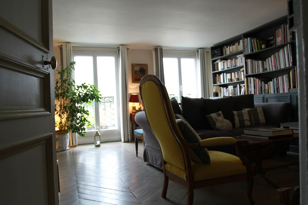 The living room (parquet flooring) with 2 large windows with perfect condition facing due west with beautiful Paris view (Montmartre) from the big balcony (a small table and 2 chairs), including a Wood bookcase, a fireplace, a table for 6 and a queen size convertible sofa-bed.