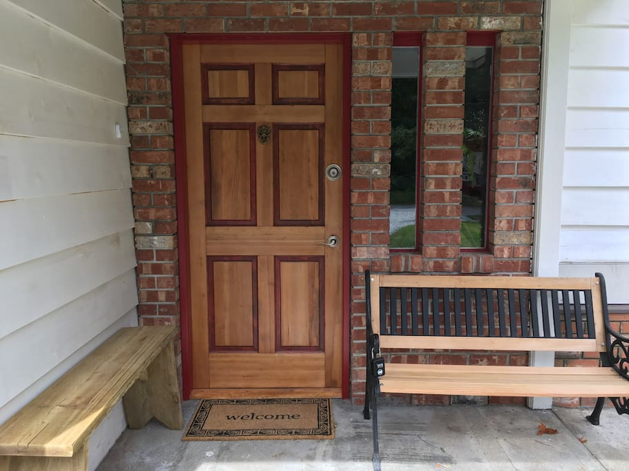 Front door with a bench beside it with the lockbox containing the house key.