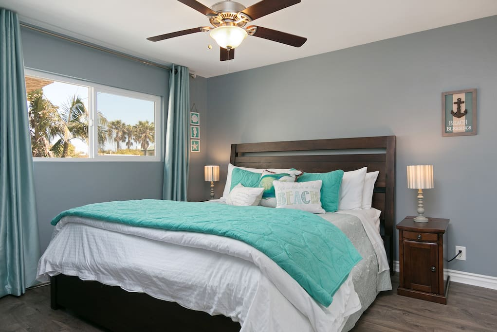 In the second bedroom, a flat screen TV is mounted on the wall and a large closet stores a roll-away twin bed.