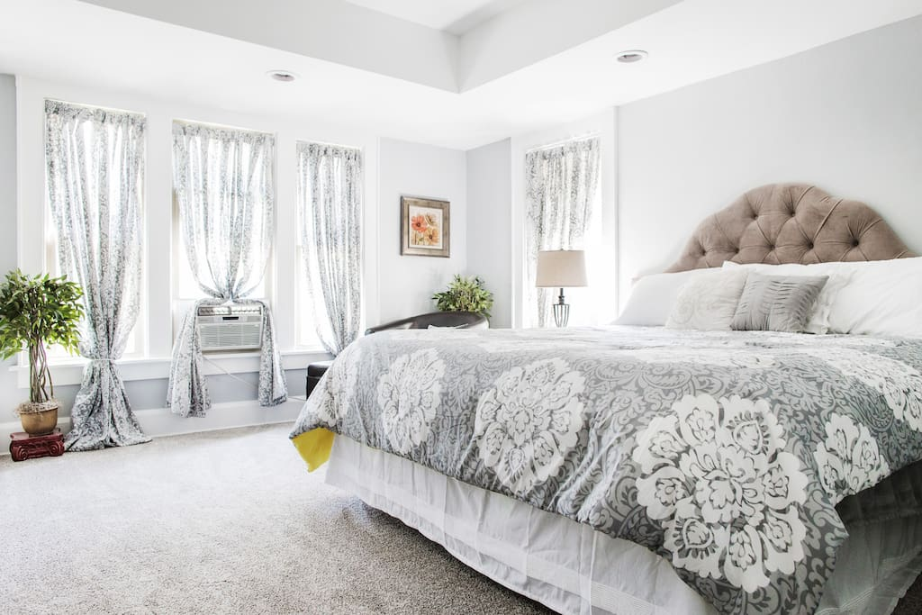 The spacious master bedroom with 4 windows has a king size bed, luxury linens, a chair with an ottoman, a tv equipped with chrome cast, closet equipped with an iron/ironing board, and an AC unit.
