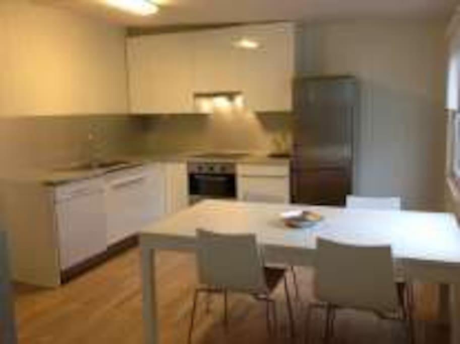 Kjøkken med bord og stoler i 2 etasje.