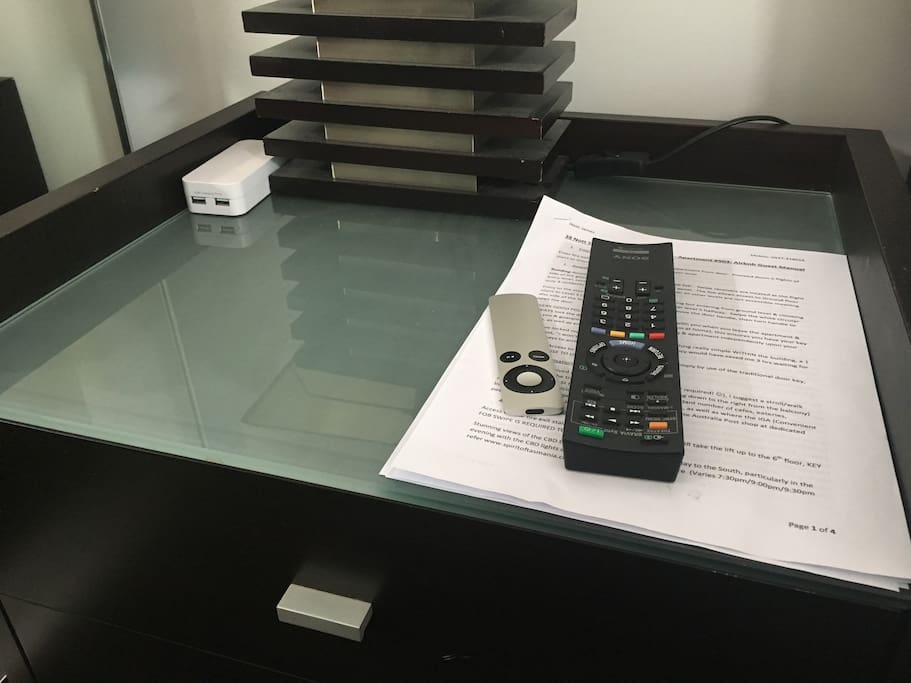 Bedside table with TV remotes, guest manual & USB power station for wash device charging.