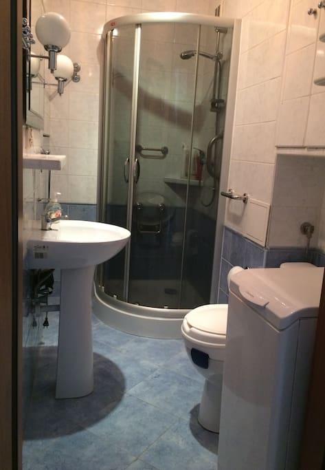 Łazienka z dwiema szafkami, pralką, prysznicem i umywalką.