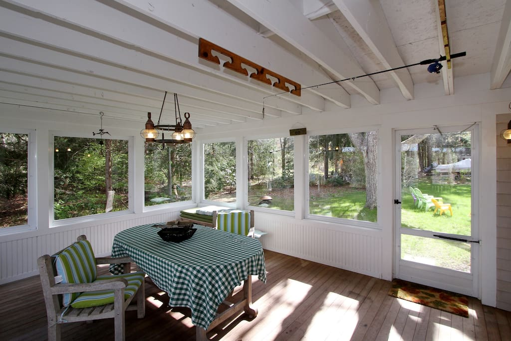 A screened-in porch offers a sunny spot for breakfast.