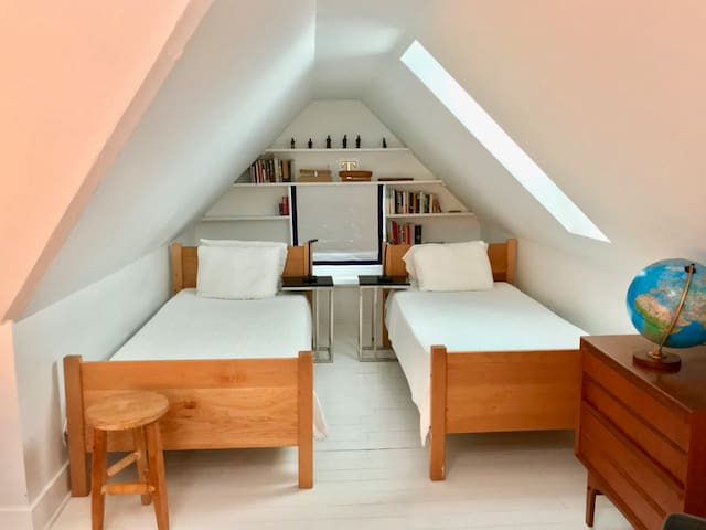 One of two 3rd floor bedrooms.  These are two extra long twins with organic natural rubber mattresses.  This room has two additional standard twins. The room is bright with all white walls and floor and plenty of sun from four skylights.