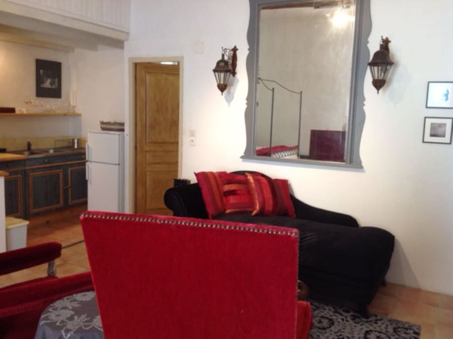 Chaise lounge, Christian Lacroix carpet and pillows, antique red velvet chairs