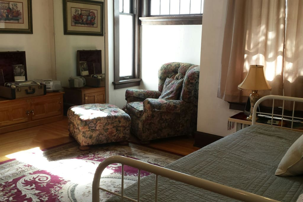 French doors open to the room. A recliner and desk also set in the sunny room.
