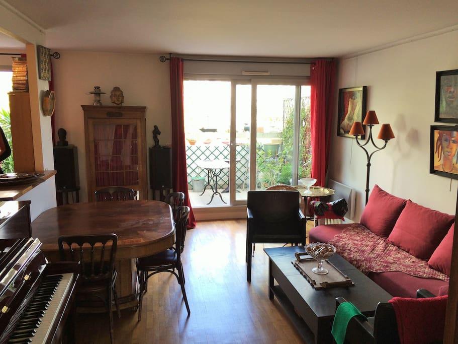 Beau séjour donnant sur terrasse, piano et canapé-lit