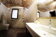 Baño 01, acceso desde la habitación accesible y salón, con ducha accesible y todo lo necesario para una persona con discapacidad.