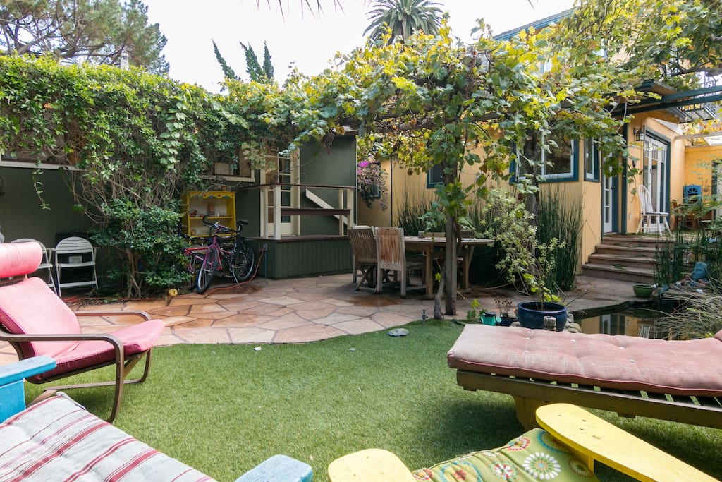 Shared backyard with dining table for 6, seating areas, a koi pond, and a grape arbor.