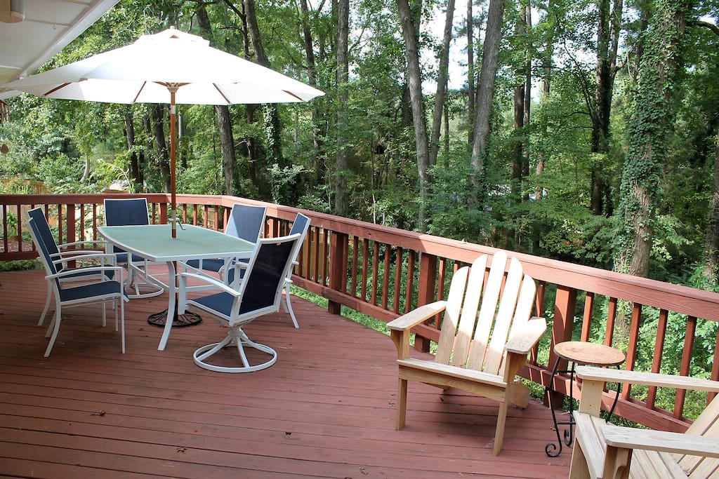 The large deck offers privacy and overlooks a wooded backyard