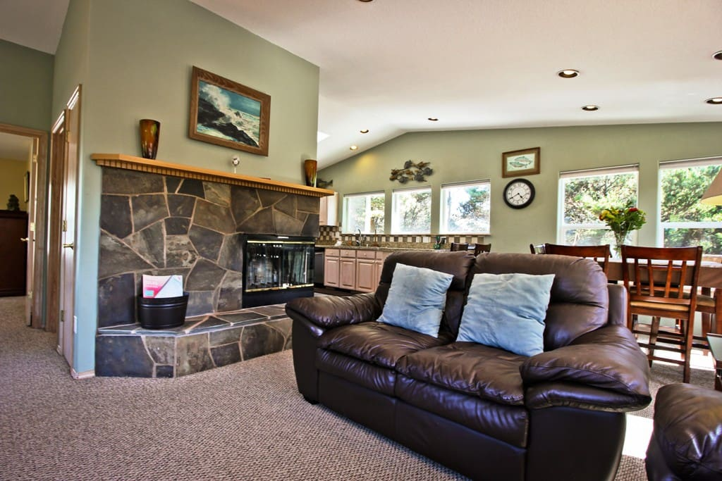 Upper level open living room with a large flat screen TV/DVD, beautiful stone double sided wood fireplace, leather couch, loveseat and over stuffed chair with access door to wrap around deck.