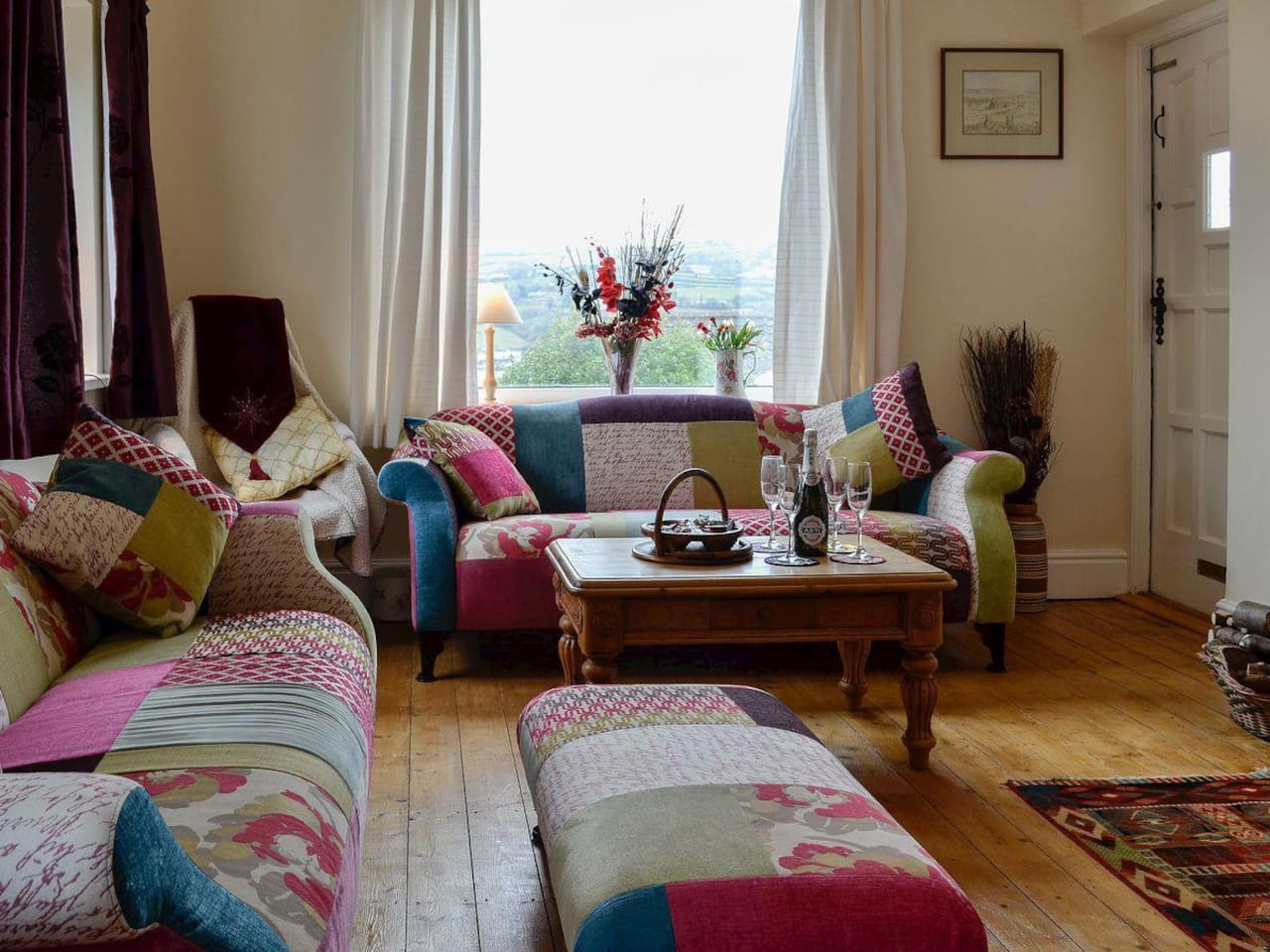 Cosy lounge with comfy sofas, log burner and balcony.