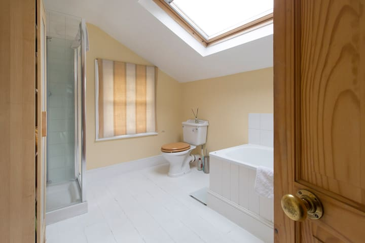 Spacious bathroom with shower, bath, basin and sink