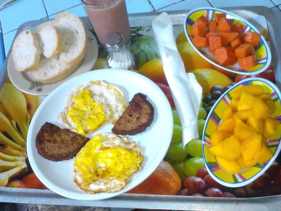 Desañuno con huevos y frutas frescas y deliciosas.