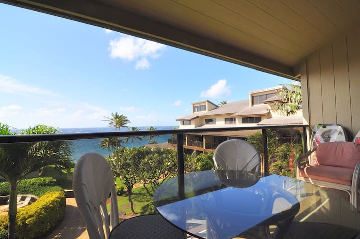 Expansive ocean view from the lanai with dining table and cushioned chairs.