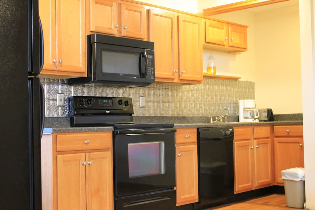 The kitchen features plenty of cabinetry, a four-burner stove, oven, microwave, refrigerator, coffee maker, toaster and basic utensils.