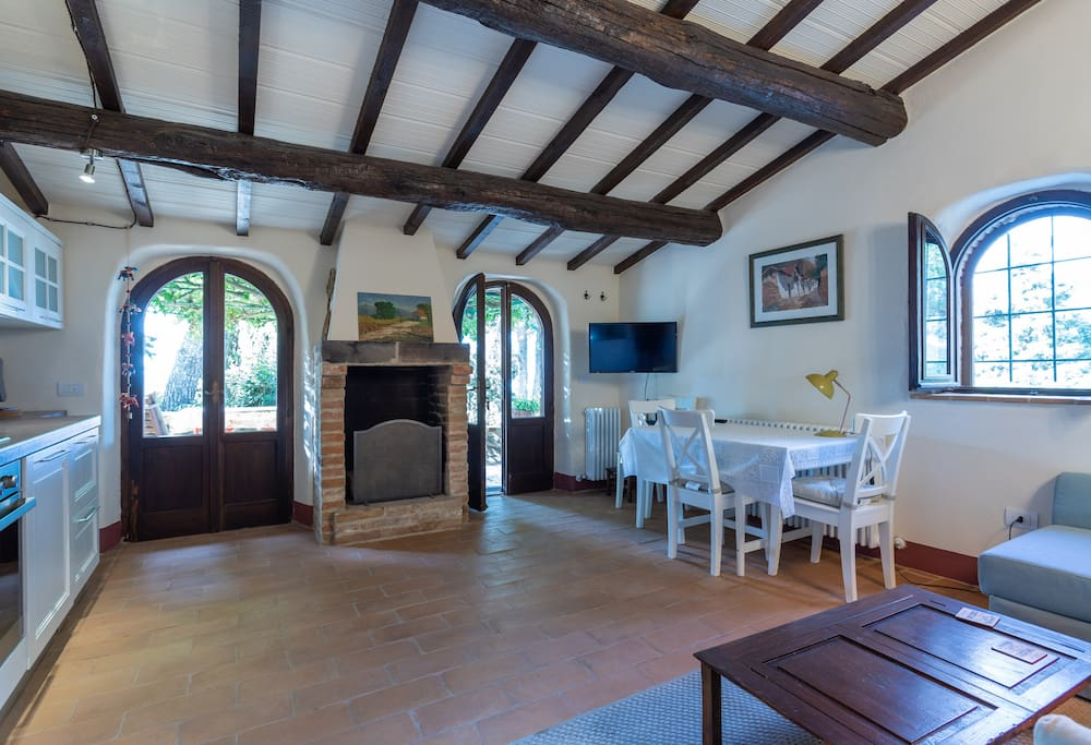 Living room and kitchen with direct access to the veranda. An authentic fireplace for cosy evenings