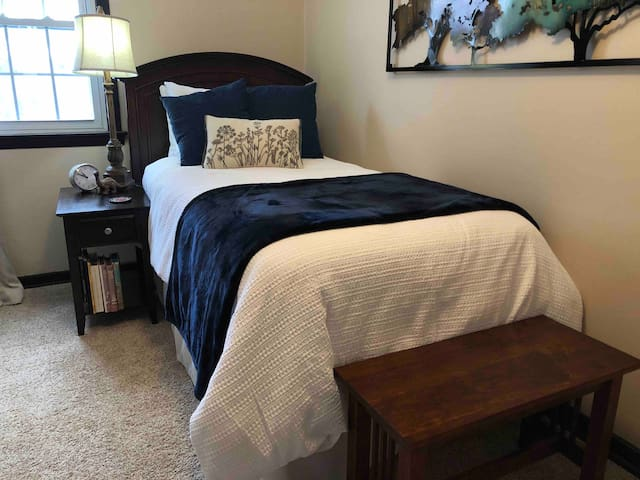 The third bedroom on the upper level has a luxury twin bed.