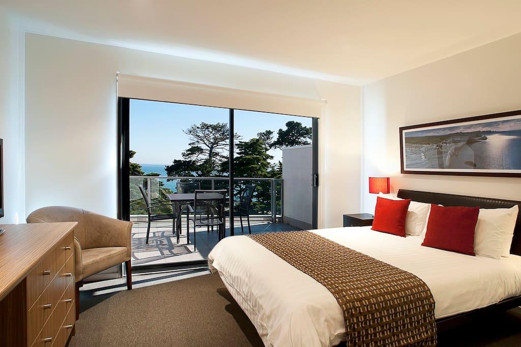 Queen bed in the main area looking over balcony