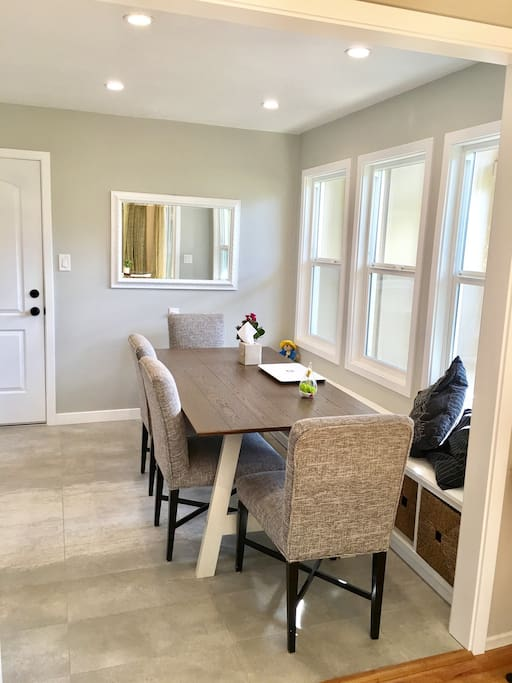 Bright and airy dinning area with window seats overlooking side yard.
