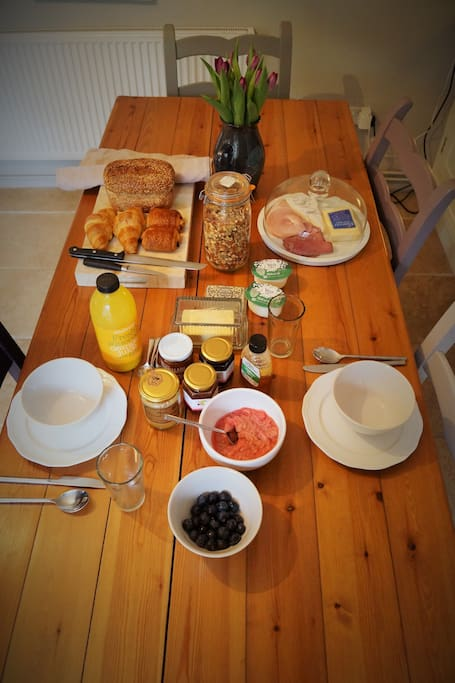 Locally sourced breakfast including freshly baked pastries, homemade granola, ham, cheeses, fresh fruit and yoghurt