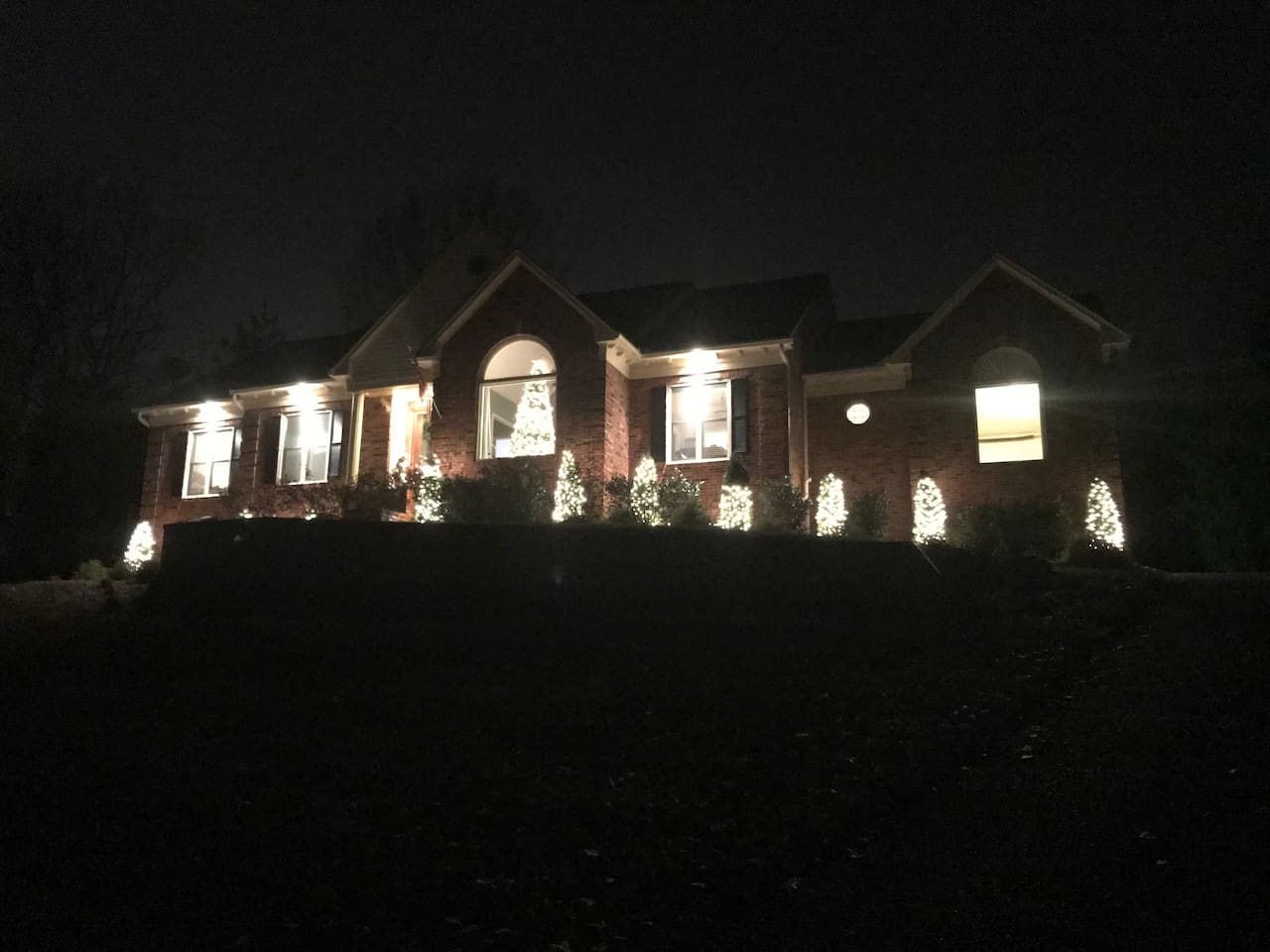 View of front of house from driveway at Christmastime