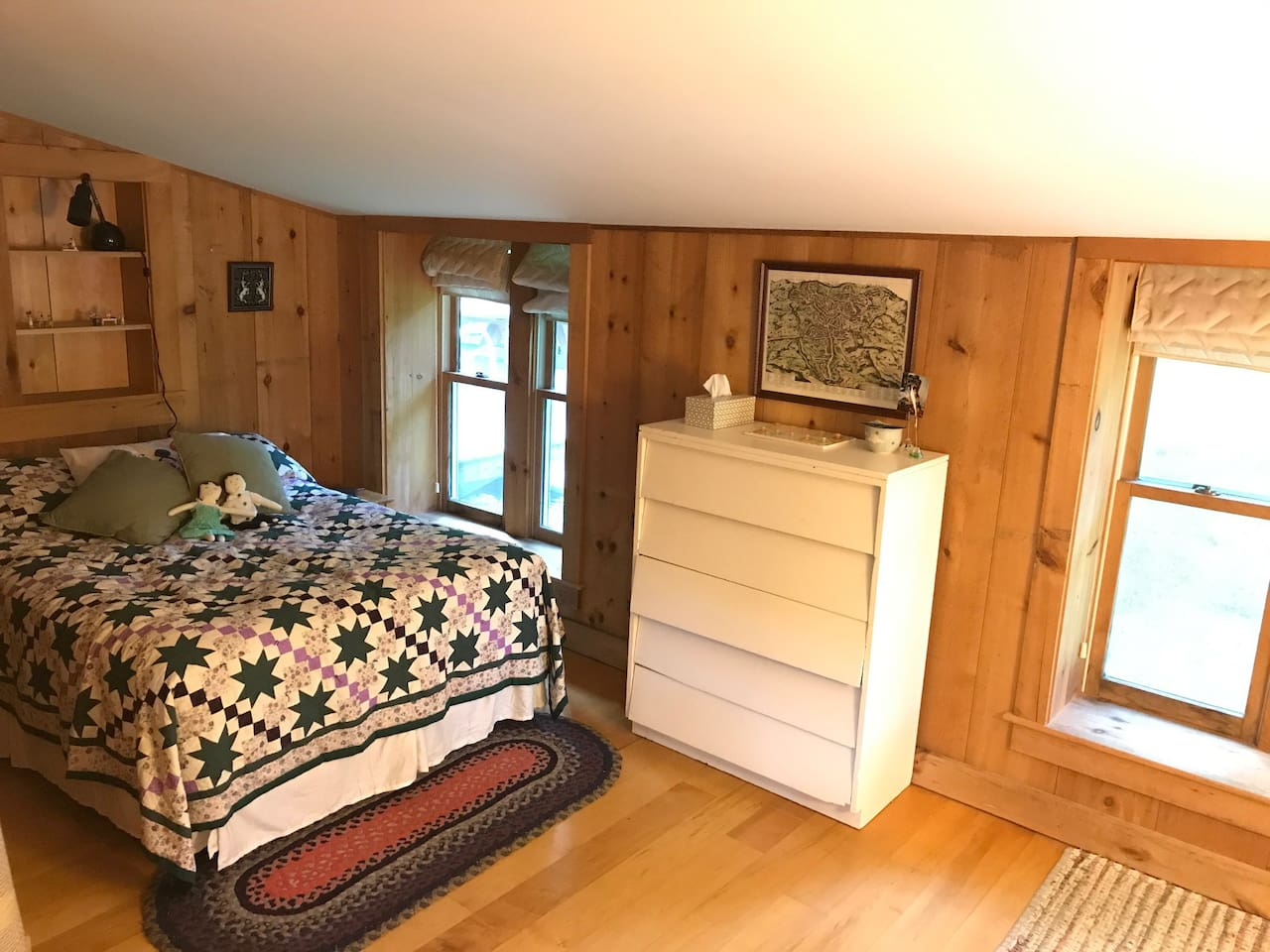 Full bed with bureau, windows look out to beautiful yard and pond