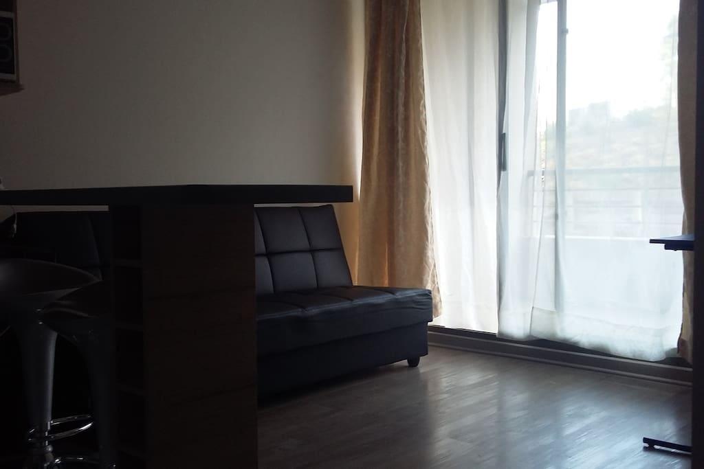 Living con futón. Mesa pequeña y silla de trabajo. Terraza con mesa y sillas. Mesón comedor.
