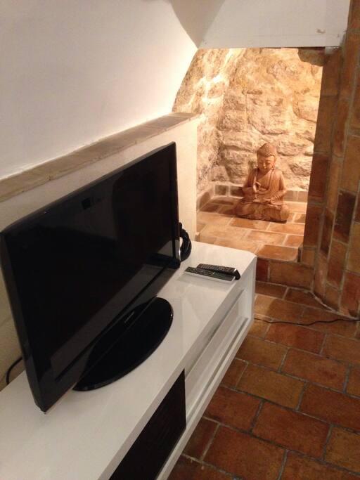 Coin télé, avec TV écran plat avec lecteur DVD, box TV et internet en Wi-Fi.